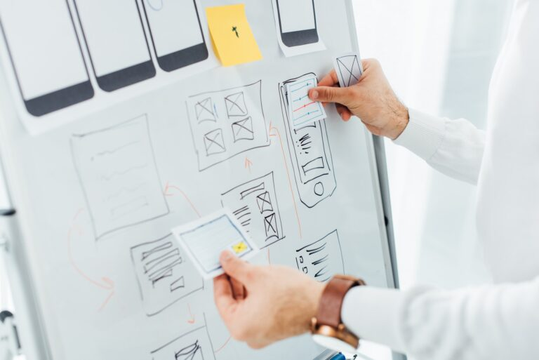 Cropped view of ux designer using layouts while creative app interface on whiteboard