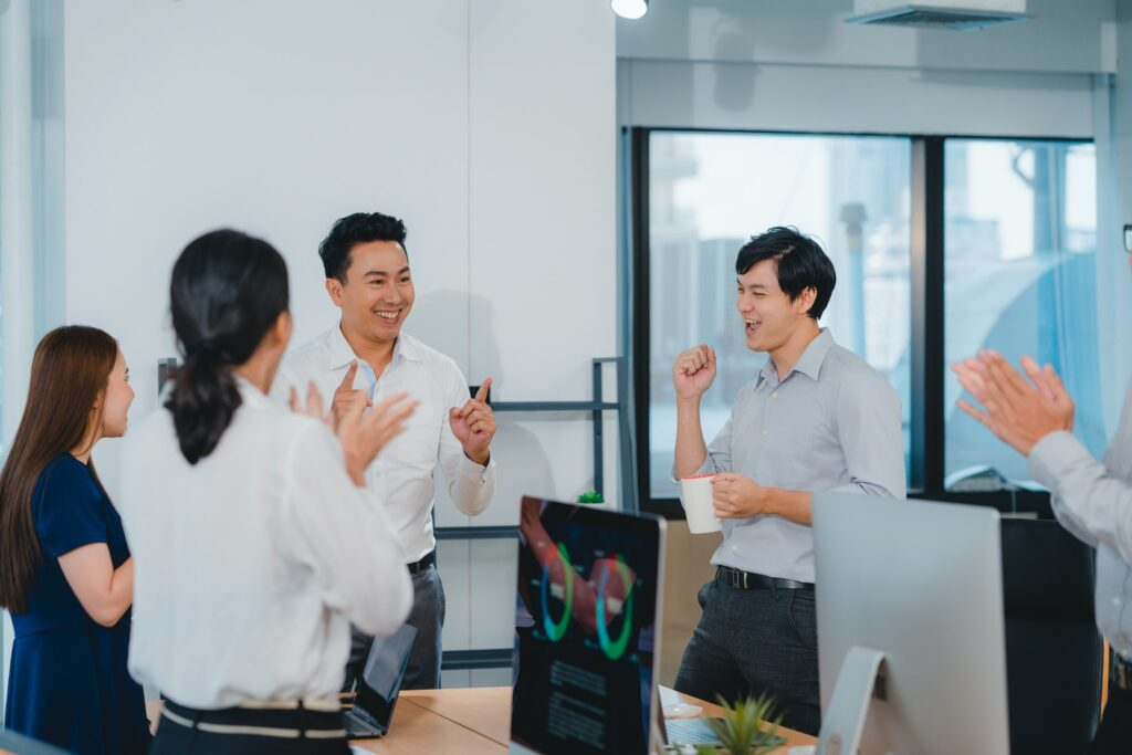 Group of young businesspeople celebrate giving five after dealing feeling happy in office.