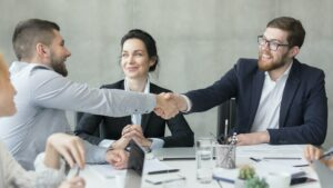 Welcome on board! Businessmen shaking hands at meeting